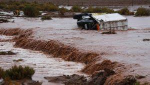 Caminhão de apoio tombado em estrada inundada